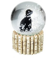 A sweet little sitting black dog in the centre of a glass snowglobe, give it a shake to watch the snow fall around it