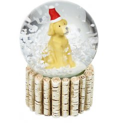 A sweet little sitting yellow dog with an added Santas Hat in the centre of a glass snowglobe