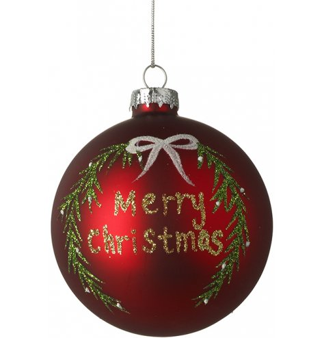 A ruby red glass bauble with a traditional wreath illustration and Merry Christmas slogan written in glitter.