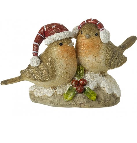 A pair of Christmas robins perched upon a stone.