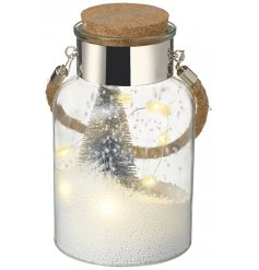 A glass jar filled with little balls of foam, silver pine trees and a warm glowing LED string