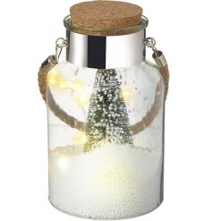 A LED illuminated jar filled with foam snow balls and a frosted green tree