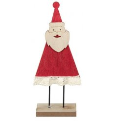 A standing wooden santa figure in a festive red tone and complete with a lace trimming