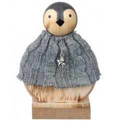 A large round wooden penguin decoration dressed up in a snuggly knitted jumper