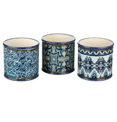A mix of 3 individually decorated ceramic pots, each set with a rustic patterned decal and blue tone