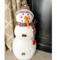 A charming little fabric snowman complete with twig arms, a carrot nose and fuzzy woollen hat