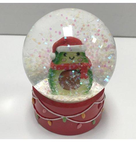 A comical festive dressed avocado within a snow globe.