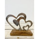 A rustic aluminium double heart decoration set upon a chunky wooden block.