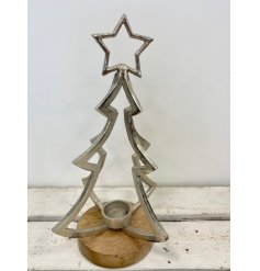 A rough luxe three-dimensional silver Christmas tree candle holder with star topper and chunky wooden base.