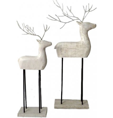 A stylish reindeer ornament with a handmade aesthetic, complete with white washed finish and tall metal legs.