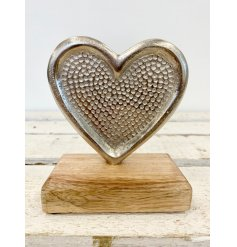 A chic silver heart ornament with a dotty decorative pattern and natural wooden base.
