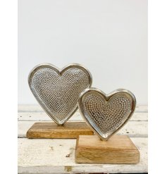A stylish silver heart ornament with a decorative pattern. Set upon a chunky wooden base making a chic interior item