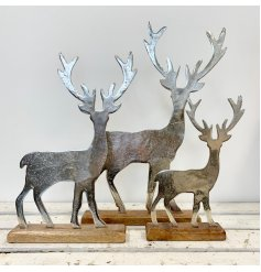 A charming silver stag ornament made from aluminium with a chunky wooden base. A rustic item with a rough luxe feel.