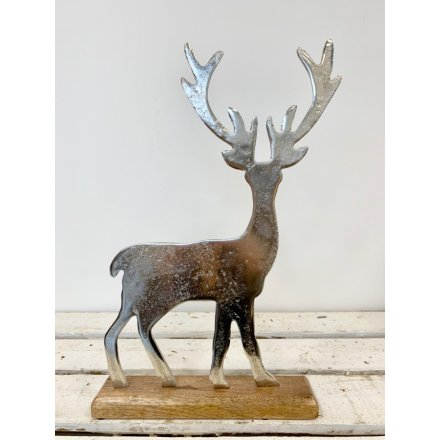 A rustic style silver stag ornament made from aluminium. Set upon a natural chunky wooden base.