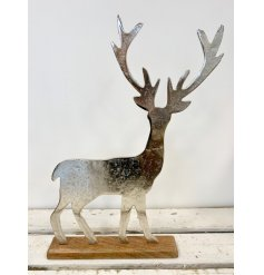 A chic silver stag ornament set upon a natural, chunky wooden base. A rustic home accessory.