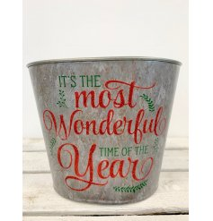 It's the most wonderful time of the year. A rustic metal planter with a seasonal red glitter slogan.