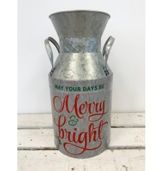 A festive milk churn with a red glitter Christmas slogan.