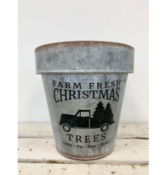 A rough luxe grey metal planter with a farm fresh Christmas slogan.
