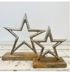 A rustic style aluminium star decoration set upon a chunky wooden base.