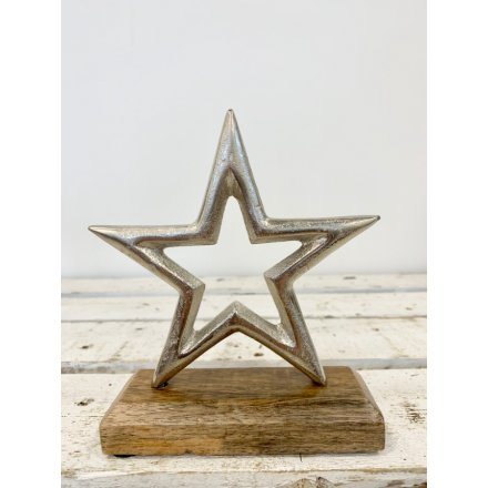 A chic aluminium star set upon a chunky wooden block. A stylish interior accessory and gift item.
