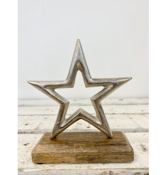 A stylish silver star decoration set upon a chunky, natural wooden block.