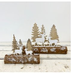 A rustic Christmas decoration. A woodland scene set upon a snow dusted log.