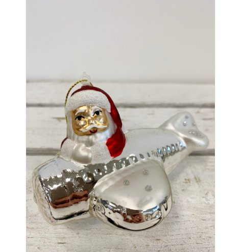 On trend vintage inspired Christmas glass bauble in the form of Father Christmas in a aeroplane.