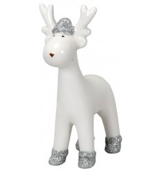 A small white toned ceramic reindeer with added silver glitter hooves and hat