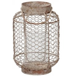 A distressed metal lantern built up with a chicken wire surround