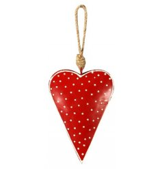 A hanging metal heart with a red and white polka dot pattern