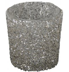 A glass candle holder covered in a super sparkly silver glitter beading