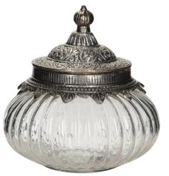 A large clear ridged glass jar with a vintage inspired metal lid for decoration