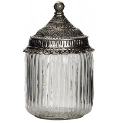A clear ridged glass jar featuring a distressed metal lid with added embossed decals