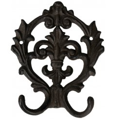 A cast iron wall hook with an added Fleur De Lis inspired pattern