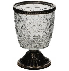 Bring a charmingly distressed vibe to your home interior with this tall glass candle pot with a footed base