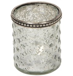 A tall glass candle holder featuring a mottled silver decal and added ridged surround