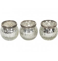An mix of 3 glass tlight holders featuring metal rims and assorted ridged decals