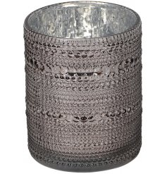 A large round ridged glass candle holder set with a mottled silver centre and tinted grey tone