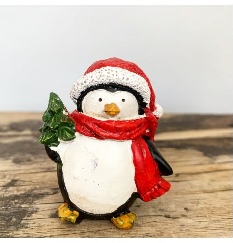 Adorable penguin figures wearing traditional red Santa hats and scarves.