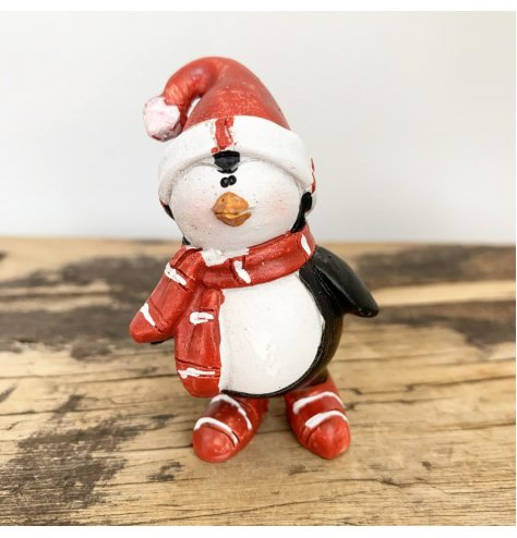 Adorable penguin figures wearing red and white striped boots and scarves, complete with Santa hats.