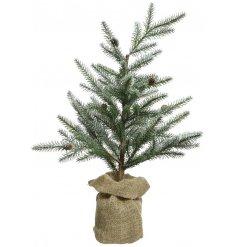 A beautifully simple artificial Pine Tree sat inside a rustic jute bag