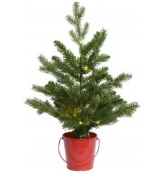 A charming Pre-Lit Pine tree sat inside a festive red toned metal bucket