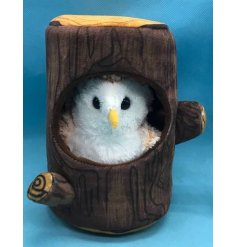 A snuggly soft toy owl complete with a cozy tree log enclosure