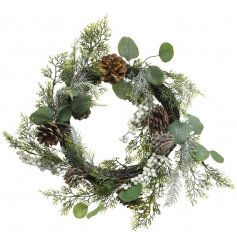 A beautiful artificial wreath covered in woodland foliage, pinecones and berries