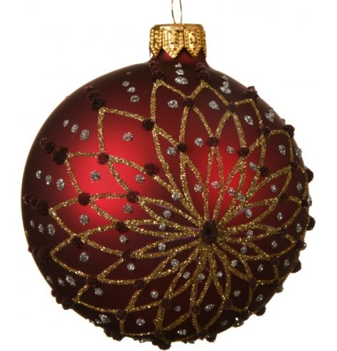 A stunning oxblood red bauble with an ornate and highly decorative glitter floral motif.