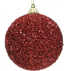 A foam based bauble covered with sparkly red toned glitter and topped with a gold hanging string