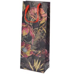 A luxurious floral gift bag in rich purple and pink hues with a touch of gold glitter and a metallic finish.