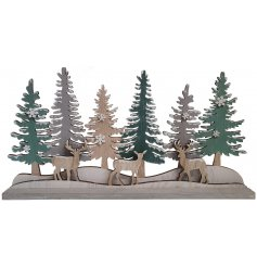 A lovely winter wonderland scene of snow covered trees and a family of deer.