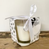 A Christmas scented candle beautifully packaged in a silver snowflake design open front box with gift tag and bow.