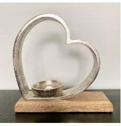 A chic and stylish metal heart tlight holder set onto a rustic wooden block